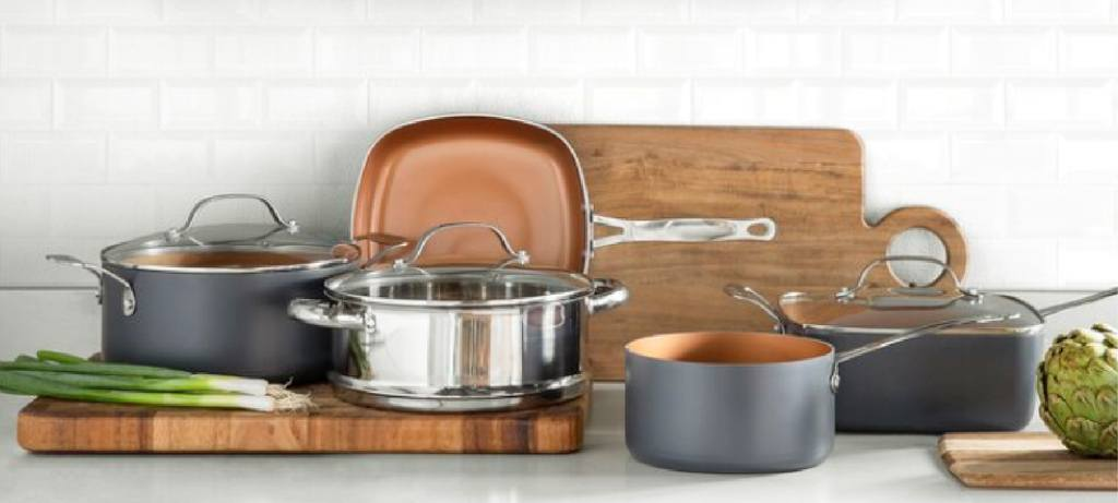 the elegant steel gotham cookware with some utensils around