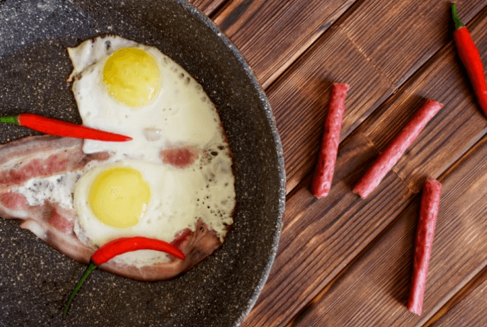 a corner of granite pan contains egg and bacon