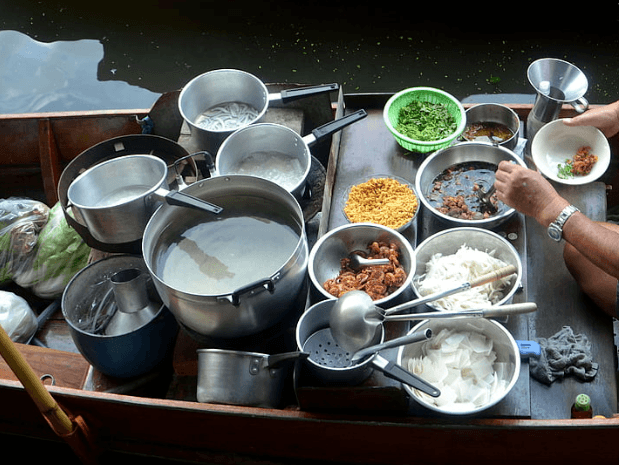 food being selling in stainless steel cookware on the floating boat