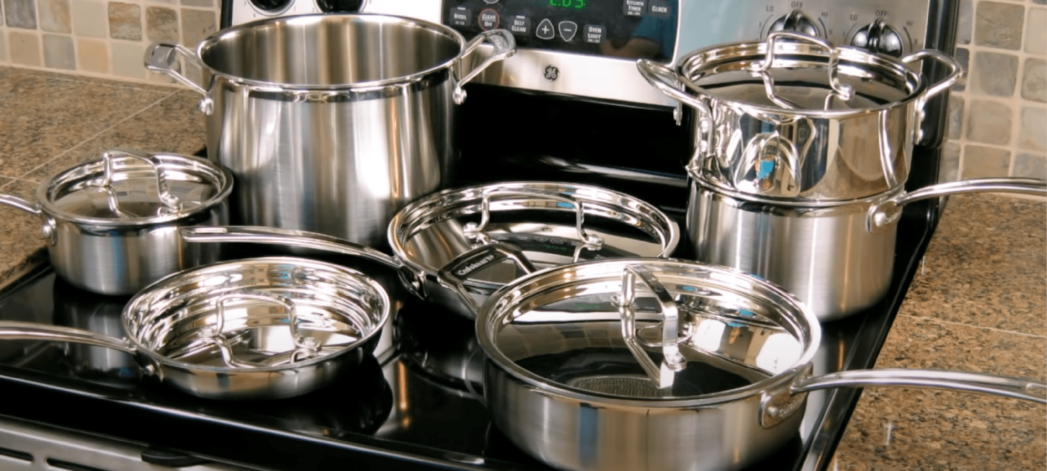 the stainless steel cookware resting on the glass stove