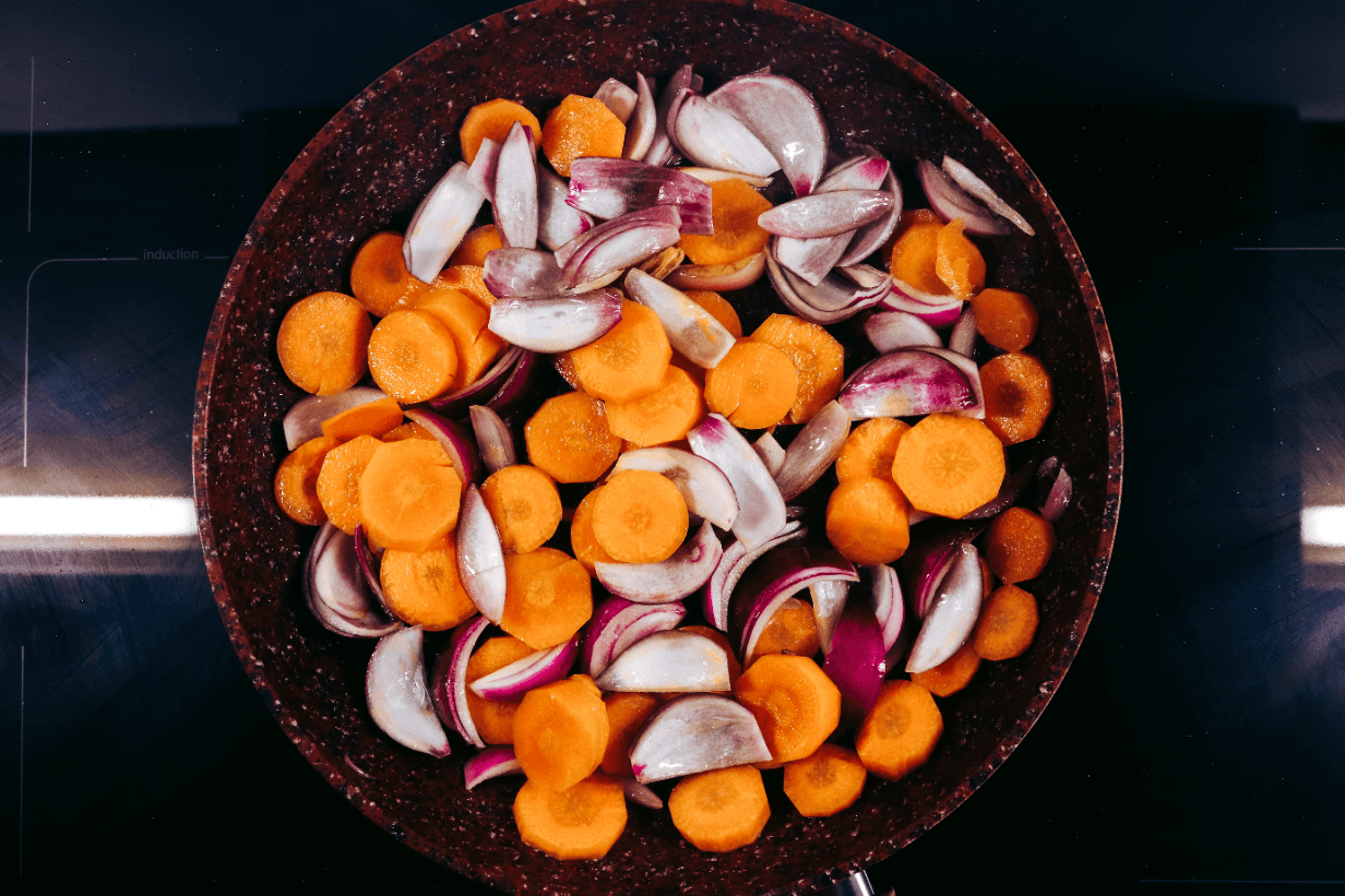 frying carrot and purple onion in a pan
