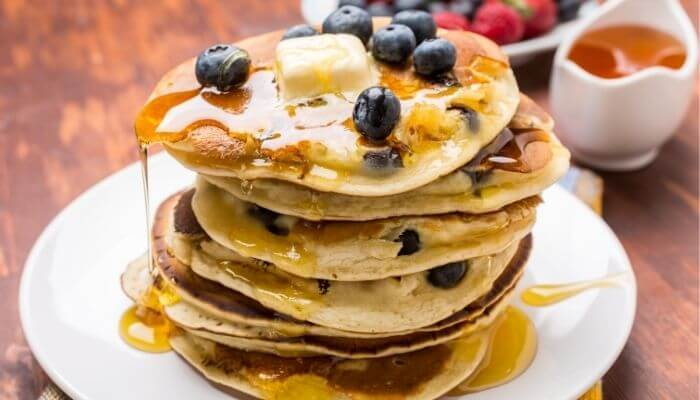 blueberry and honey pancakes on a table