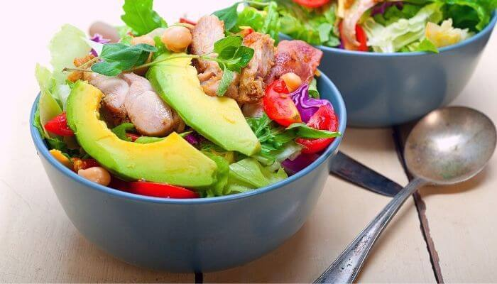 chicken with avocado salad resting in a bowl