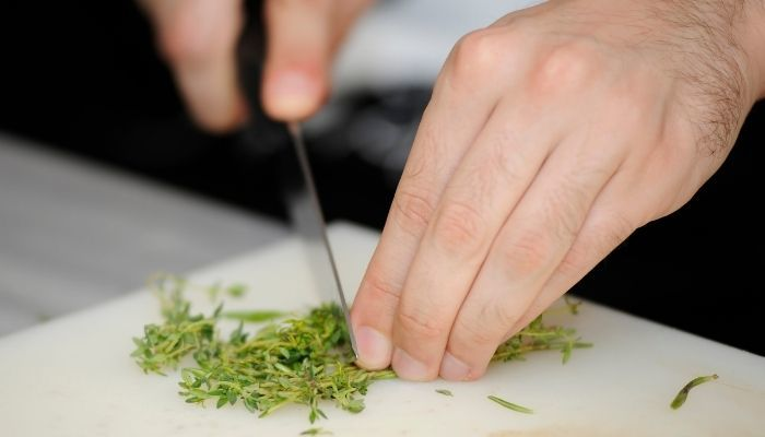 chopping thyme on cutting board