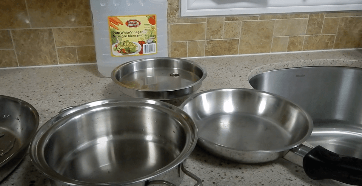 Stainless cookware and vinegar placed on table