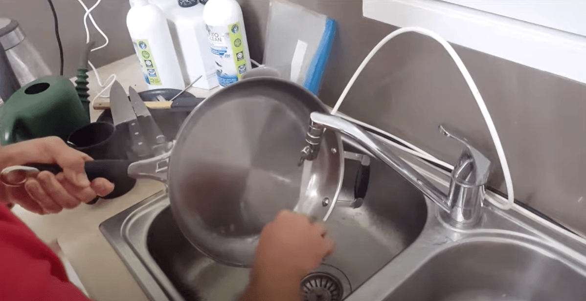 A woman is cleaning a pan